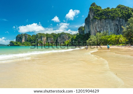 Railay Beach West. Cliffs covered with jungles and clear water during a beautiful sunny day in July (low season). Krabi, Thailand