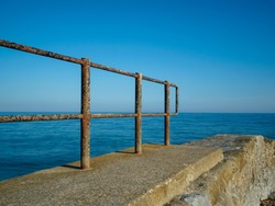 Railings made of rusty metal leading out to the sea taken with long exposure to smooth the ocean and creating leading lines with the hand rail