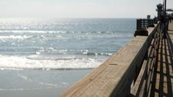 Railings of old wooden pier, people walking on waterfront boardwalk, Oceanside beach atmosphere, California coast USA. Defocused seascape, pacificocean water waves. Los Angeles summertime vacations.