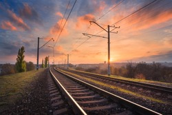 Railroad against beautiful sky at sunset. Industrial landscape with railway station, colorful blue sky with red  clouds, trees and green grass, yellow sunlight. Railway junction. Heavy industry.
