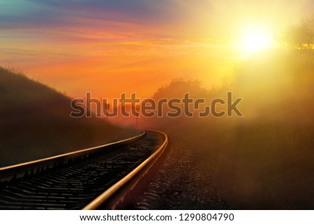 Railroad against beautiful sky at sunset. Industrial landscape with railway station, colorful blue sky, trees and grass, yellow sunlight. Railway junction. Heavy industry. Railways. Cargo shipping #1290804790