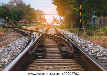 Railroad against beautiful sky at sunset. Industrial landscape with railway station, colorful blue sky, trees and grass, yellow sunlight. Railway junction. Heavy industry. Railways.Thailand