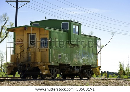 Railroad caboose sits on a siding gathering graffiti near a cemetery.