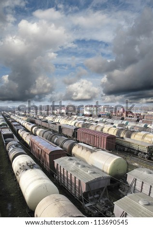 Railroad cars on a railway station. Cargo transportation. Storm clouds above train