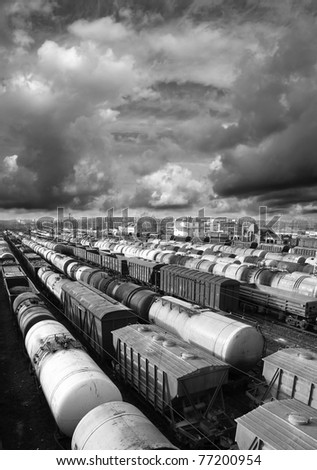 Railroad cars on a railway station. Cargo transportation. Storm clouds above train. Black and white photo