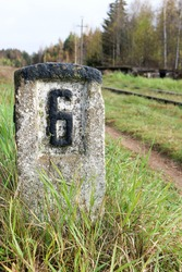 railroad concrete kilometer sign on abandoned railway with the autumn forest on the background