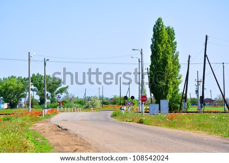Railroad crossing, equipped with a semaphore in the midst of blossoming poppy field