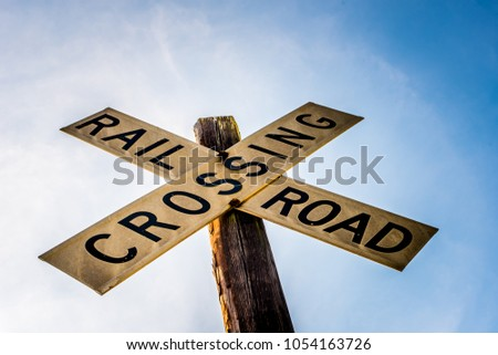 Vintage railroad crossing sign and post at the tracks Images