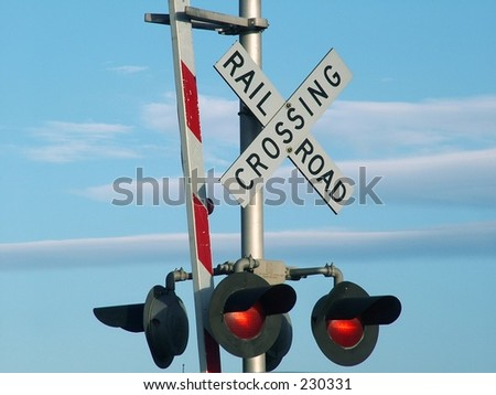 Railroad Crossing sign against blue sky with clouds