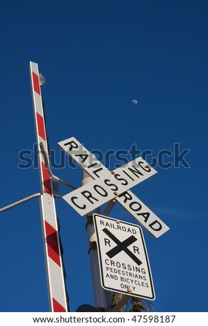 Railroad crossing sign against brilliant blue sky with moon shining in the distant sky