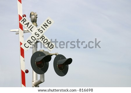 Railroad crossing sign with two warning lights and the red & white road barrier raised. Photo ID: RailroadSign00001