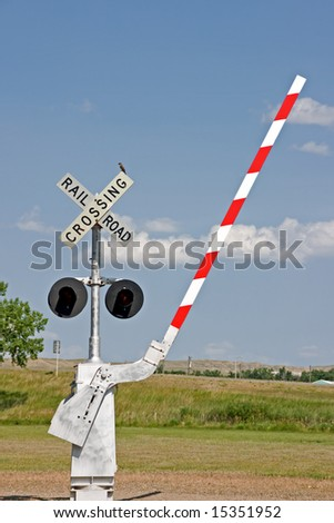 Railroad crossing signal with lights, barrier, and a bird on the sign at a museum