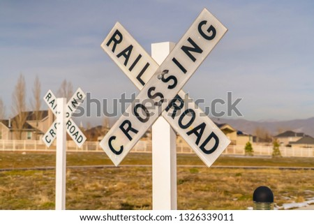 Railroad Crossing signs against homes and sky #1326339011