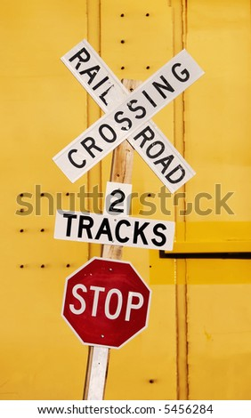 Railroad crossing stop sign against a yellow train car.