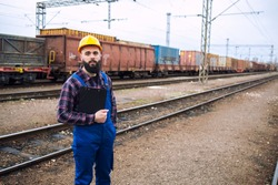 Railroad freight transportation. Portrait of railroader man worker with clipboard standing by the railroad tracks and cargo freight train in the background.