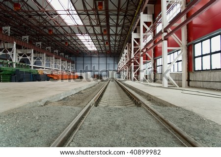 Railroad going into the distance in hangar near from hardware. Metal columns and ceiling.
