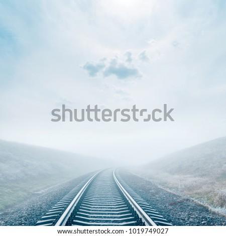 railroad in fog. sun in misty cloudy sky