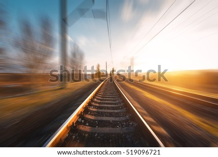 Railroad in motion at sunset. Railway station with motion blur effect against beautiful blue sky, Industrial concept background. Railroad travel, railway tourism. Blurred railway. Transportation