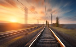Railroad in motion at sunset. Railway station with motion blur effect against colorful blue sky, Industrial concept background. Railroad travel, railway tourism. Blurred railway. Transportation