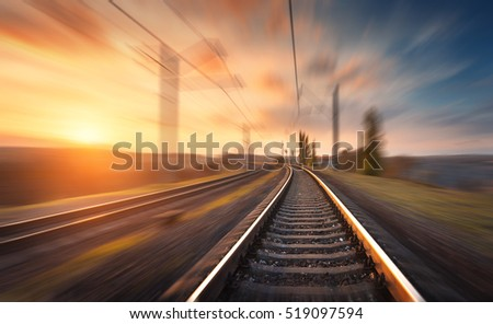 Railroad in motion at sunset. Railway station with motion blur effect against colorful blue sky, Industrial concept background. Railroad travel, railway tourism. Blurred railway. Transportation #519097594