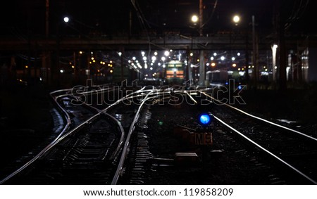 Railroad night scene with blue traffic light and cargo trains. Selective focus on semaphore