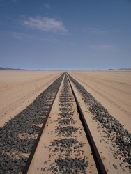 Railroad reaching straight to the horizon amidst a sandy desert landscape, with a few clouds against the blue sky.
