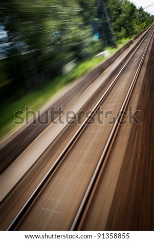 Railroad seen from a fast moving train. (motion blurred image; color toned image)