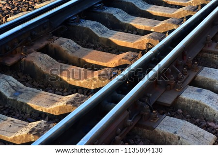 Railroad switch closeup. Rails on cracked old concrete sleepers
