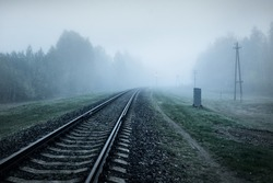 Railroad track in a thick white fog, forest in the background. Concept landscape. Freight and passenger transportation, industry, business, communications, environmental damage. Monochrome, mystery