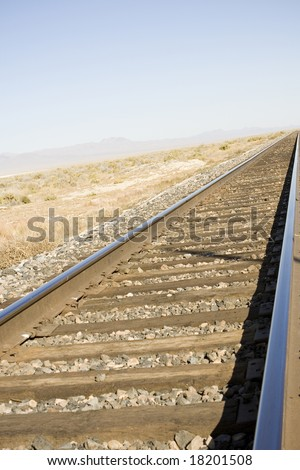 Railroad track in the Nevada desert with vanishing point and some blue sky for copy space.