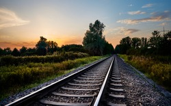 Railroad track leading into distance at sunset. Railway transportation in countryside nature, travel background.