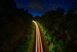 Railroad tracks at night with light trails