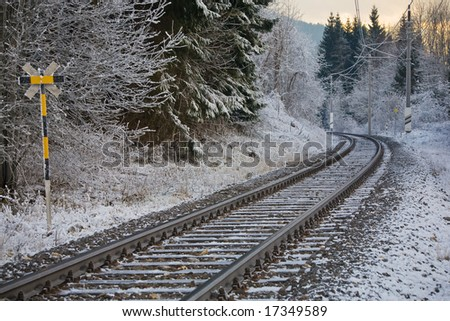 Railroad tracks in winter landscape at sunset.