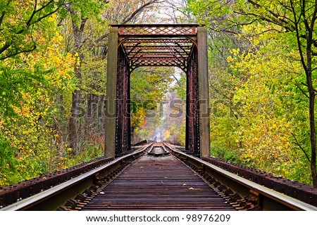 Railroad tracks lead through an iron trestle (bridge) toward infinity with changing fall leaves surrounding.