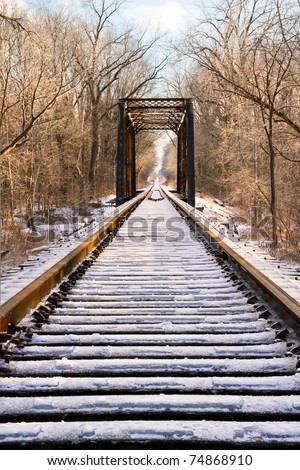 Railroad tracks leading to a trestle and everything covered in a layer of thick ice