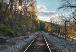 Railroad tracks pass through the forests near Ellicott City, Maryland. The sun sets behind the lush green trees in the springtime.