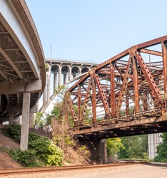 Railroad tracks under three bridges, an old rusted railroad bridge, the Braddock Avenue overpass and the East Pittsburgh bridge that US Route 30 runs upon