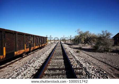 Railroad Tracks. View of empty railroad tracks  leading off into the horizon & framed by an empty coal tender & manzanita trees.