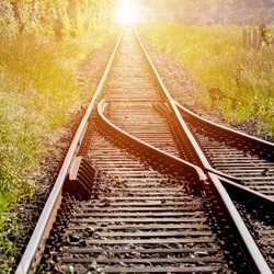 Railroad tracks, with a switch in the foreground, leading to infinity with the red light of the rising sun in the center of the background