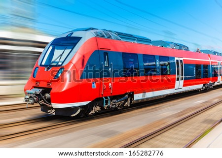 Railroad travel and railway tourism transportation industrial concept: scenic summer view of modern high speed passenger commuter train on tracks with motion blur effect
