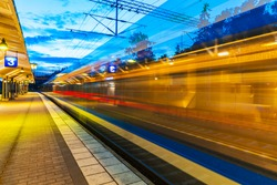 Railroad travel and transportation industry business concept: summer evening view of high speed commuter passenger train departing from railway station platform with motion blur effect