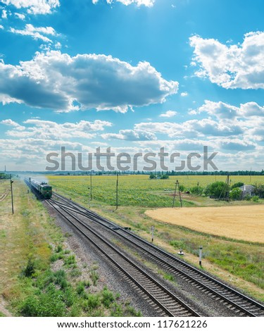 railroad with train under cloudy sky