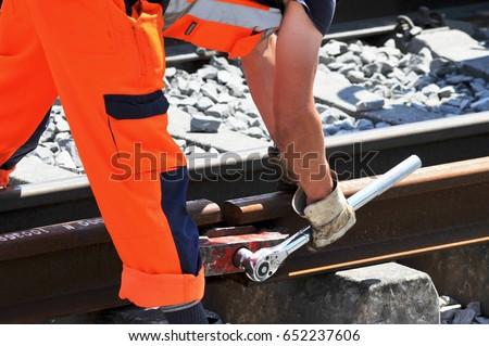 Railroad Worker fixes two Single Rails
