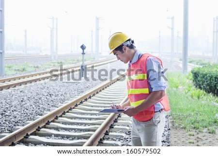 Railroad worker in protective work wear checking the railroad tracks