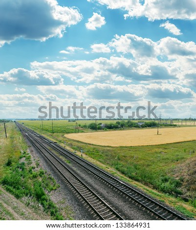 railroads to horizon and cloudy sky