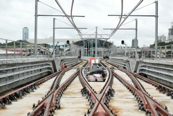 Rails for trains, in the construction of the Metro de Panama. San Miguelito Station in the background