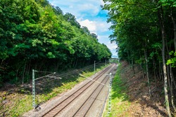 Rails of railway network leading through green forest  enabling ecologically friendly transport of passengers via electricity and electrification