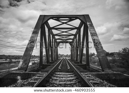 railway and old steel bridge with sky and clouds on background ,filtered image, selective focus,HDR black and white color picture style,grain added,dark edges