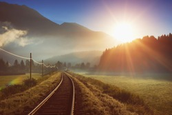 Railway and train in the Alpes at sunrise