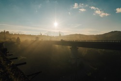 Railway bridge in the fog at sunrise. Silhouette of a bridge on the river on a background of sky and sun.